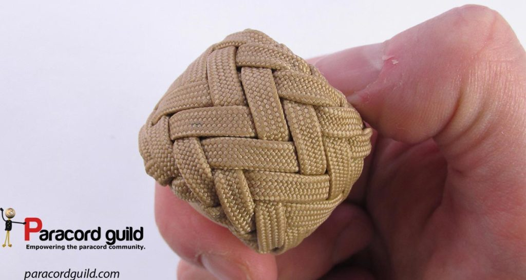 The knot tighten around a wooden sphere.